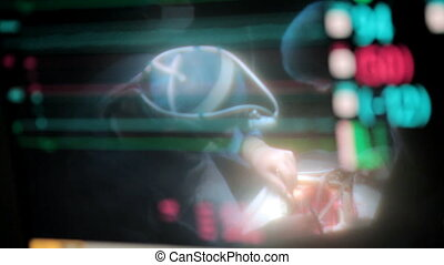 Reflection in the monitor of surgeon doing open heart surgery
