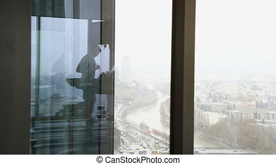 Reflection of a man walking on treadmill at high floor gym...