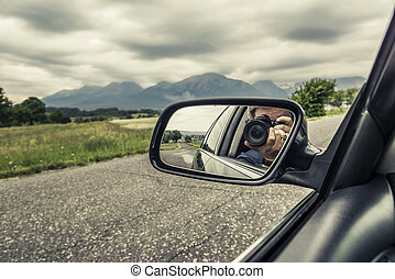 Reflection of a photographer with a camera in the rear view mirror of a car.