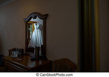 Reflection of a wedding dress in a mirror