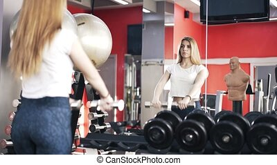 Reflection of a woman doing dumbbell exercise in a gym