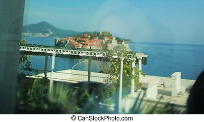 Reflection of beautiful bride in the window with amazing view of Montenegro, Budva
