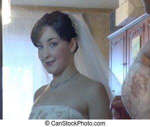 reflection of bride readjusting her wedding veil in mirror -...