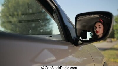 Reflection of cute girl in rearview mirror of car -...