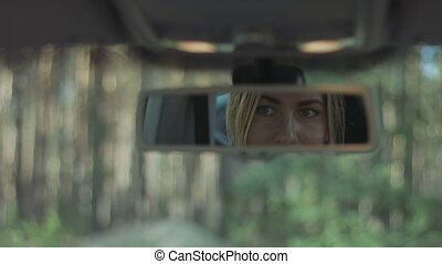 Reflection of cute woman in car rear-view mirror