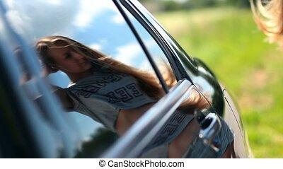 Reflection of cute woman in car side window
