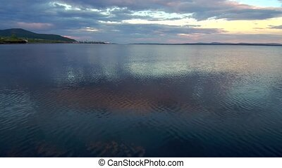 Reflection of evening clouds on the sea surface. The span of the drone above the water. Beautiful northern nature at sunset