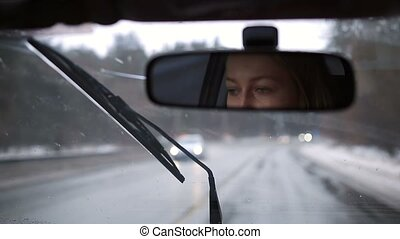 Reflection of girl driving car in rearview mirror