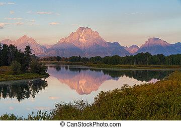 Reflection of Grand Teton range at the waters at Oxbow bend during sunrise at Grand Teton National Park