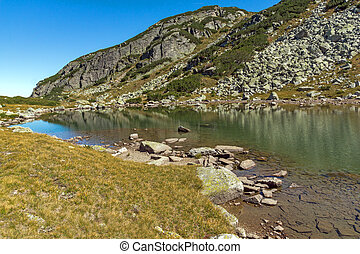 Reflection of green hills in small Lake, Rila Mountain
