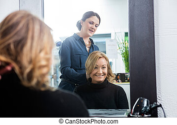 Reflection Of Hairdresser Setting Customer's Hair