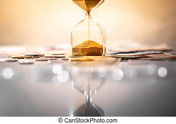 Reflection of hourglass with currency on glowing table.