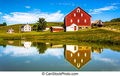 Reflection of house and barn in a small pond, in rural York ...