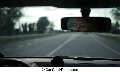 Reflection of lovely woman in car rear-view mirror