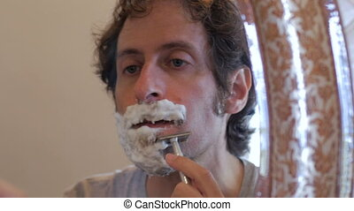 Reflection of man using a safety razor to shave a beard -...