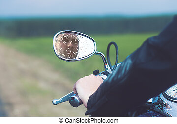 Reflection of Motorcycle Driver in Rearview Mirror