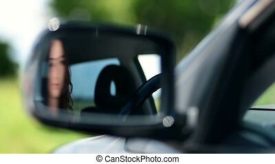 Reflection of pretty woman in car side-view mirror