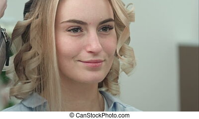 Reflection of smiling young woman with blond hair in salon mirror having hair styled