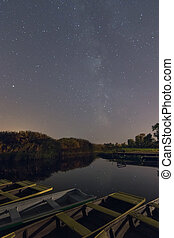 Reflection of stars and trees in the lake at night. Marina With Boats