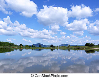 Reflection of the cloudy blue sky in the lake surface