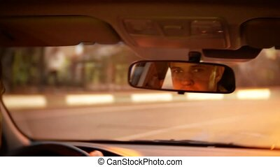 reflection of the driver of the man in the rearview mirror....