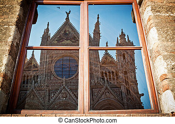 The Duomo of Siena reflected in a window of the opposite palace (Santa Maria della Scala).