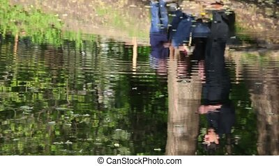 Reflection of the family in the water of the river