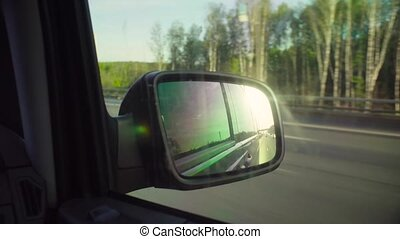 Reflection of the road in rearview mirror of a car -...