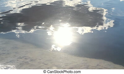 Reflection of the sunny sky with clouds in the salt brine lake