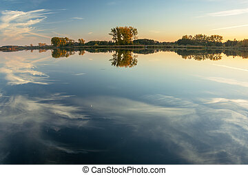 Reflection of white clouds in the water of a calm lake