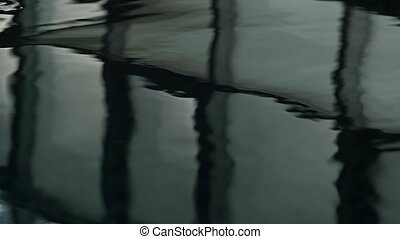 reflection of windows in swimming pool. dark rippled water....