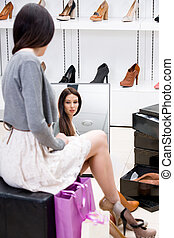 Reflection of woman trying on high heeled shoes