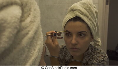 Reflection of young beautiful woman with towel on head applying her make-up mascara after taking a shower, looking in a mirror