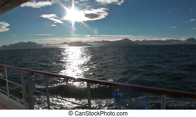 Reflection sun in water surface on background of snowy mountains and deck yacht.