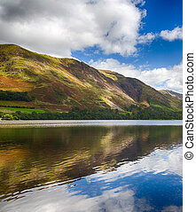 Mountains reflect into Buttermere calm lake in English Lake District