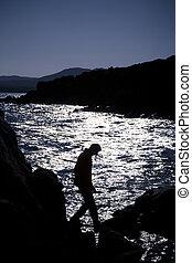Reflections - man hiking climbing on the rocks near the sea...