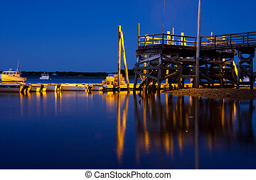 Reflections of an elevated dock at sunset.