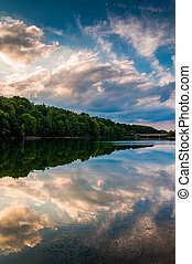 Reflections of clouds and trees at sunset in Lake Marburg, Codorus State Park, Pennsylvania.