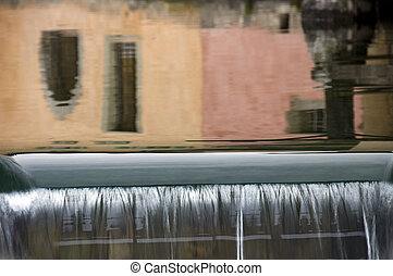 Reflections of colored walls and waterfall in Annecy