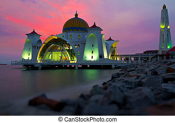 Reflections of famous floating mosque on water of sea in Malacca, Malaysia, Asia.