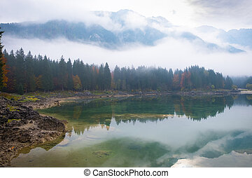 Reflections of foggy forest on lake Laghi Fusine in autumn