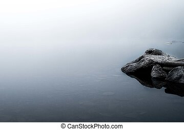 Reflections of rocks in a foggy lake