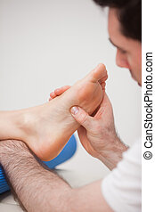 Reflexologist massaging the foot of his patient in a room
