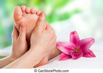Close up of hands massaging female foot.