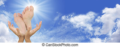 Wide Blue Sky background with outstretched healing hands and underside of feet with sunburst behind toe