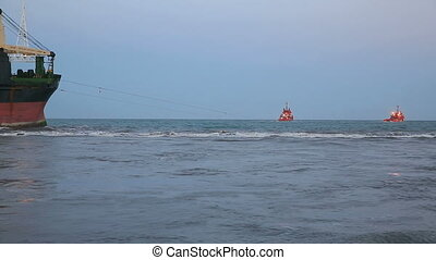 Refloating - several tugs refloating stranded ship
