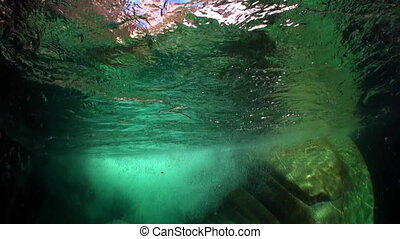 Refraction of sunlight underwater on smooth stones of river...