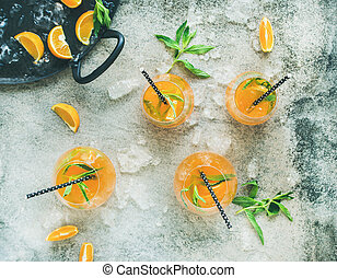 Refreshing alcoholic summer cocktail in glasses, concrete background, top view