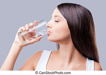 Refreshing and useful. Beautiful young woman drinking water...