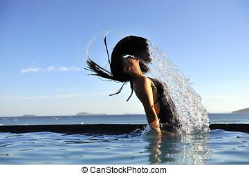 Refreshing - Beautiful swimsuit model splashing water on...
